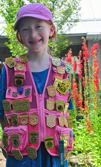 A girl wearing a vest with dozens of junior ranger badges pinned to it
