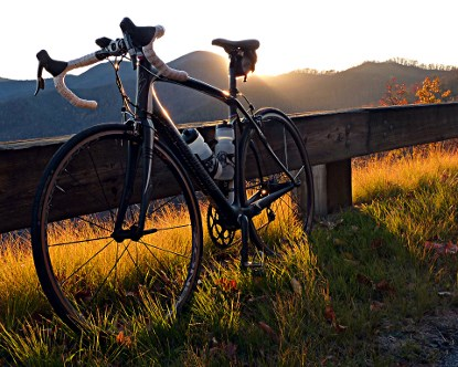 A bicycle leans against a Parkway guard rail at sunset