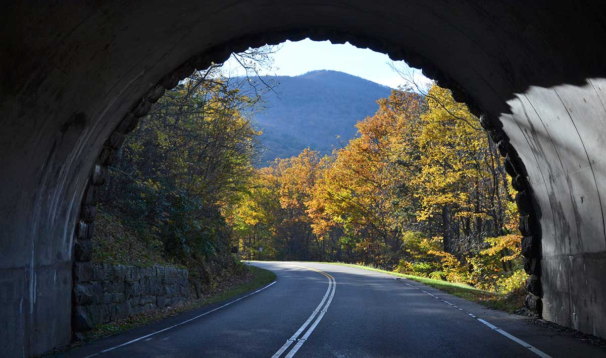 Looking out of a tunnel on the parkway. The sides of the tunnel frame a view of a mountain in the distance and trees cloaked in fall colors lining the roadway.