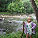 a young hiker stands by the river