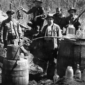 historic photo of officers posing at a moonshine still