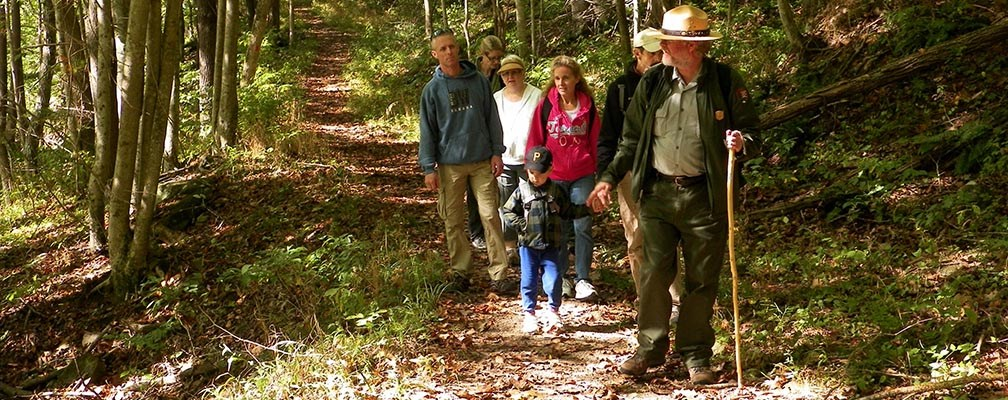 ranger leading a hike on a forested trail