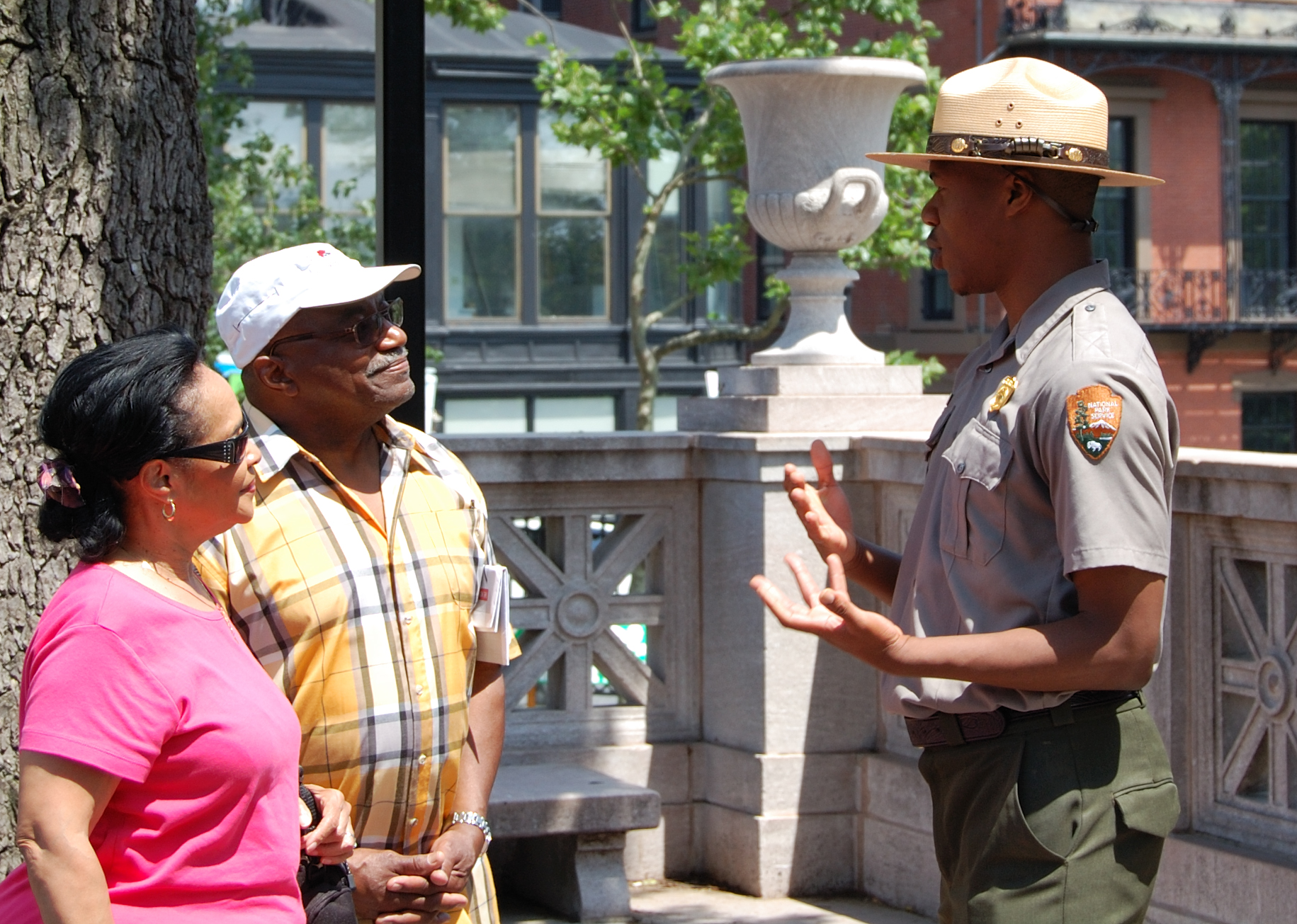 Park Ranger speaking with visitors about the Boston area and Boston African American NHS. They are speaking at the Robert Gould Shaw Memorial.