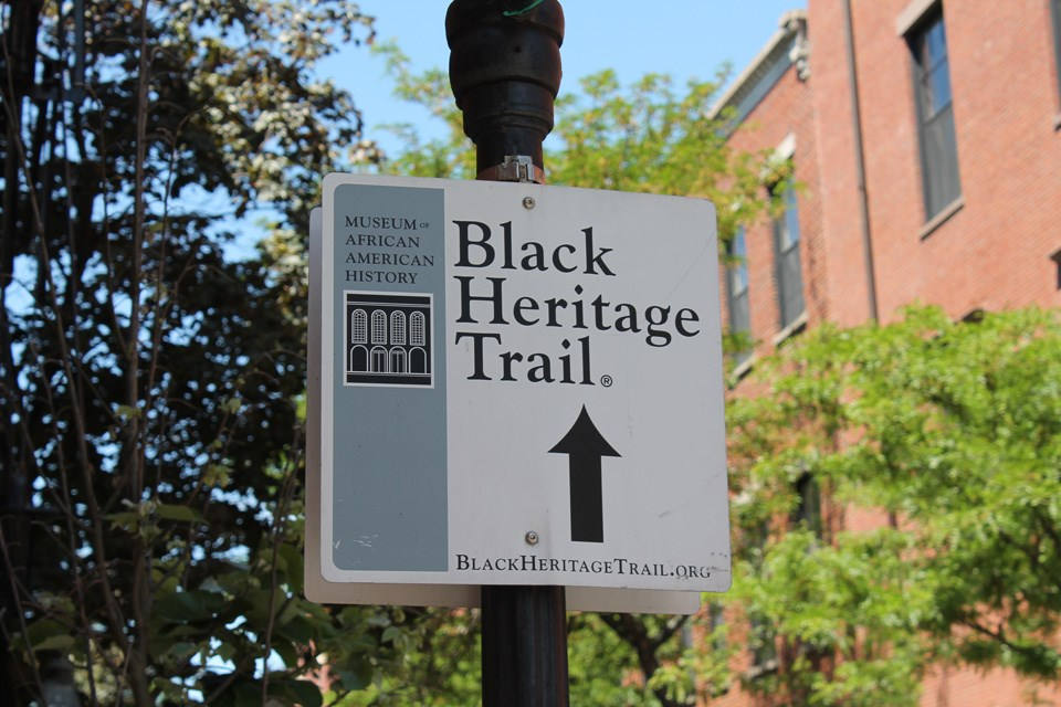 "Photograph of a cast iron gas lamp with a steel street sign with the words ""Black Heritage Trail"" and an arrow pointing ahead."