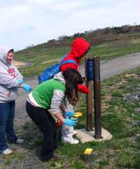 Girl Scouts refurbish wayfinding signs.