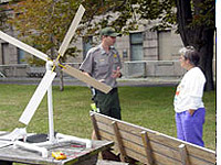 Photo of ranger and visitor with windmill model.