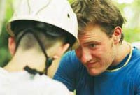 A climbing instructor prepares a student for his next challenge.