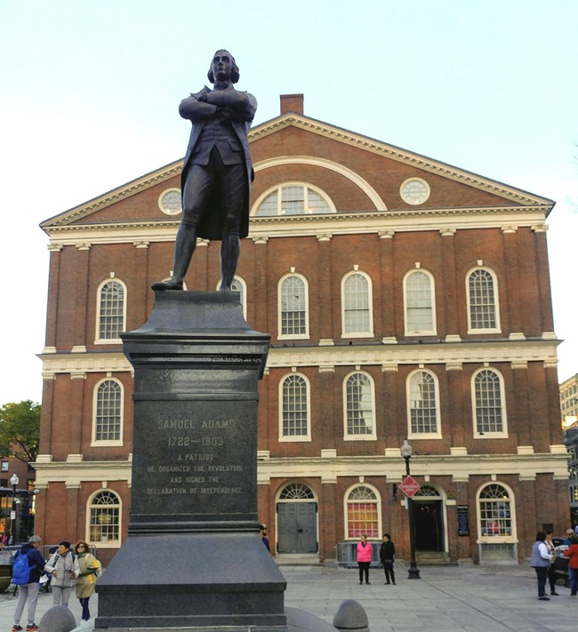 A bronze statue in front of the red brick Faneuil Hall.