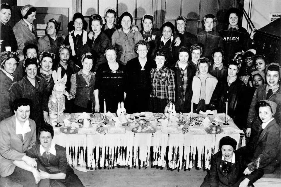 Black and white photograph of women shipyard workers around a table. Women are wearing working clothes and posing for the picture.
