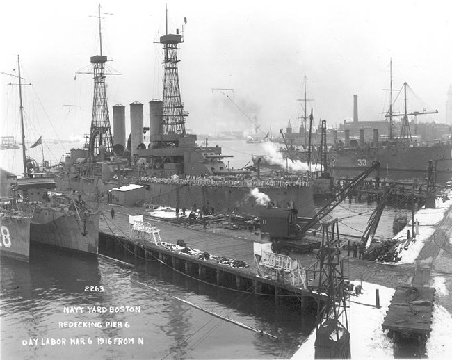 Photograph of warships of different classes moored to the wooden pier 6. Snow is covering parts of the ground.
