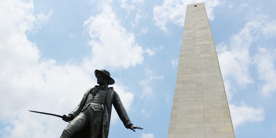 Photograph of the granite Bunker Hill monument with the bronze statue of William Prescott carrying a sword in the foreground