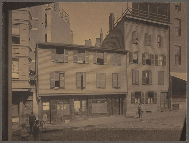 Black and white photograph of the Paul Revere House as a three story building serving as a tenement and storefront.