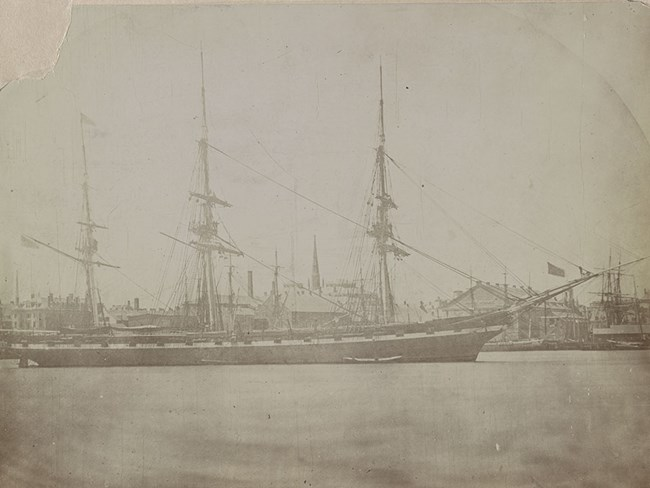 Photograph of USS Hartford with her masts fitted out. She is in a harbor with a waterfront area in th background.