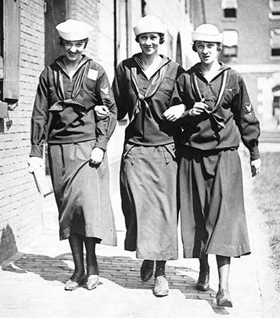 "Black and white photgraph of three women walking through the navy yard in their ""Yeomanette"" uniforms"
