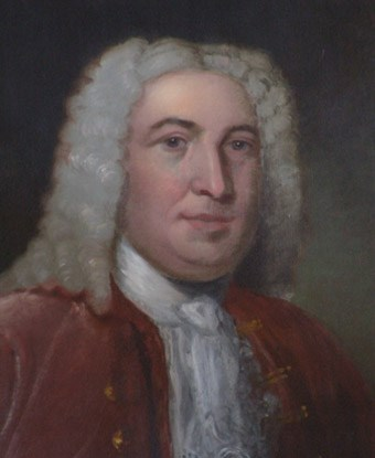 Close up of Peter Faneuil wearing a red coat, frilly neckwear, and a powdered white wig.