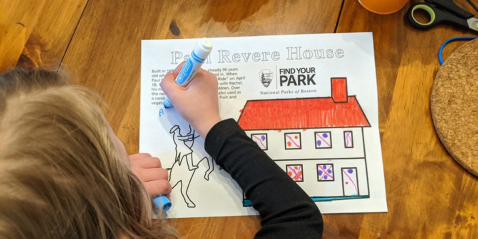 "Child at table with marker coloring in a coloring sheet. Sheet reads ""Paul Revere House"" and features a two story house and a man on a rearing horse."