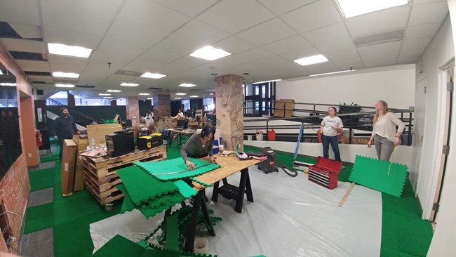 Photograph of park staff members measuring and cutting green carpet tiles in an open room.