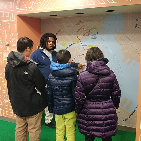 Park staff member stands in front of large map while showing three visitors the distance between sites.