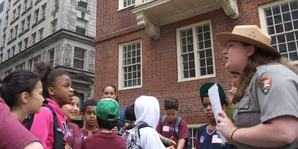 A park ranger leads a tour for children outside the Old State House