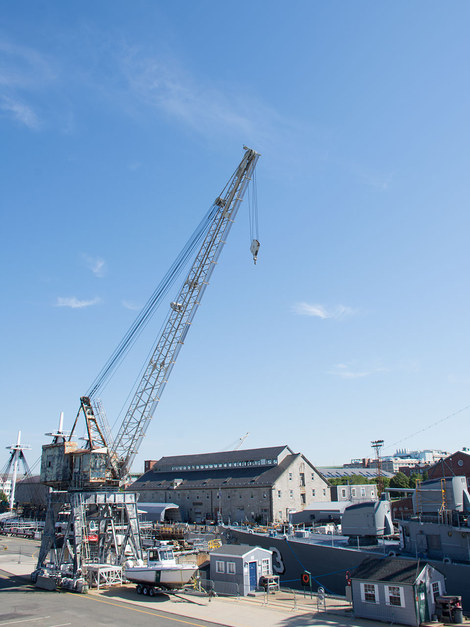 A steel portal crane towers over the bow of a docked warship. Equipment and tool sheds are nearby on the pier. A granite warehouse stands in the background.