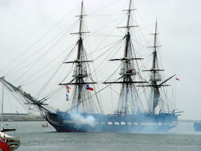 USS Constitution firing her cannons.