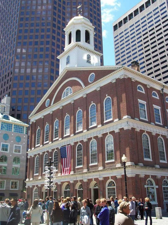 Faneuil Hall is a four-story brick building with arched windows. The top of the hall has a while cupola with a gold dome and a grasshopper weathervane. Crowds of people pass in front of the hall.