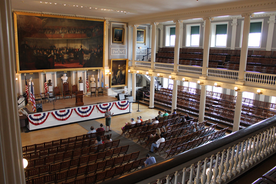 The Great Hall of Faneuil Hall is an open meeting space with a gallery level. Doric and Ionic columns support the room. Portraiture and busts decorate the space.