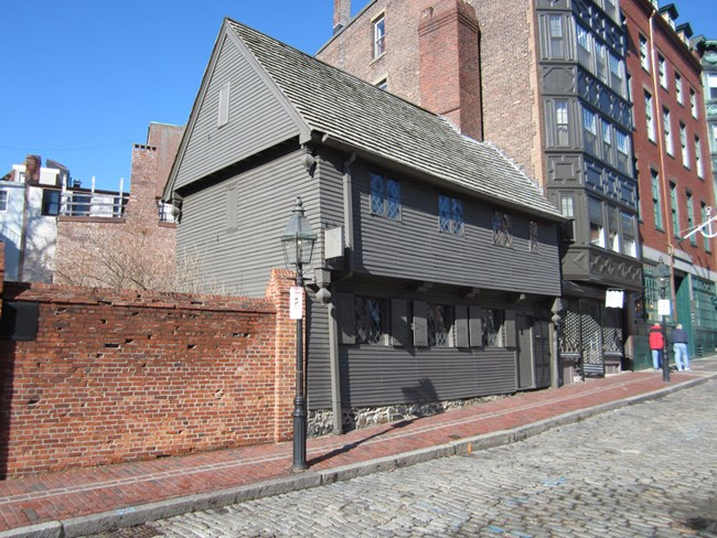The Revere House is a two story wooden building painted gray. The high pitched roof is cedar shingle with a chimney on the right end of the house. The windows are panes of diamond-shaped glass. Shutters are only on the first floor windows.