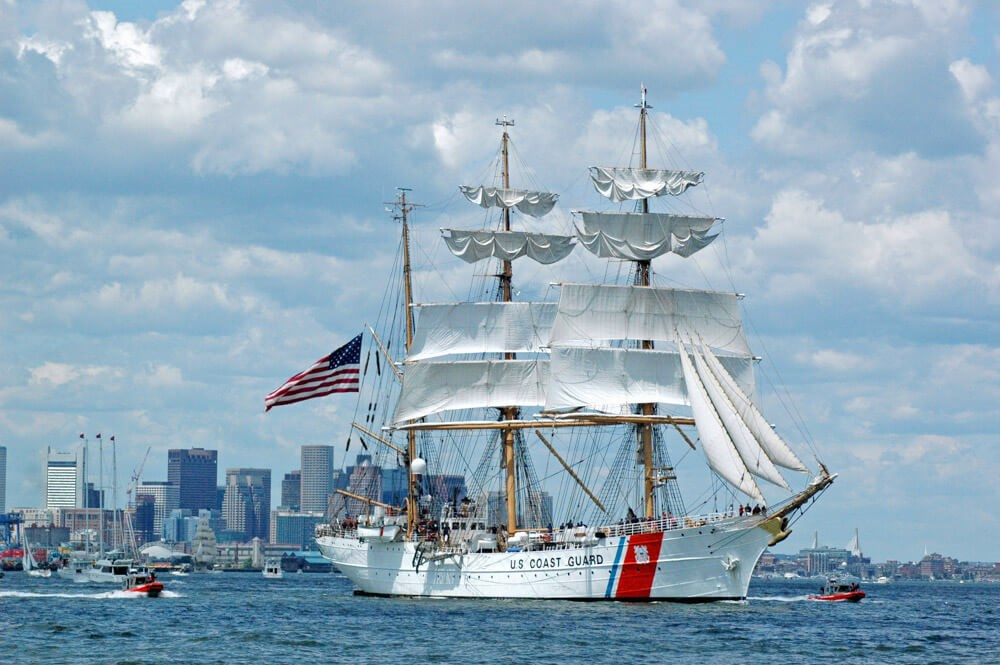 Tall ship with sails and white hull sails in Boston Harbor