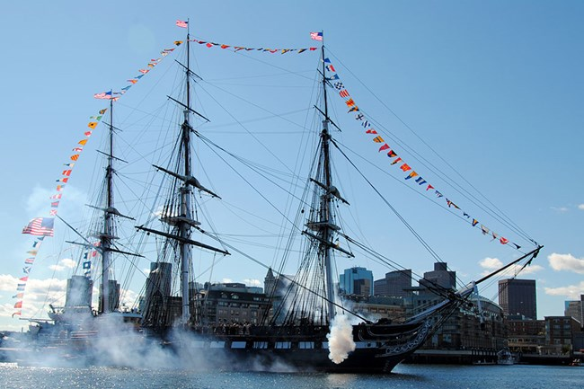 USS CONSTITUTION in Boston Harbor displaying full-dress signal flags draped from bow to stern over her three masts. Signal guns are firing in salute.