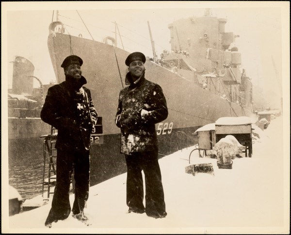 Two USS Mason Sailors on the pier near their ship in a snowstorm