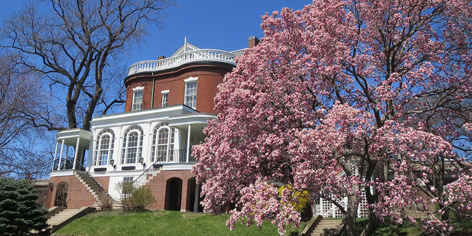 Photograph of the Commandant's House with a tree with pink blossoms in foreground.