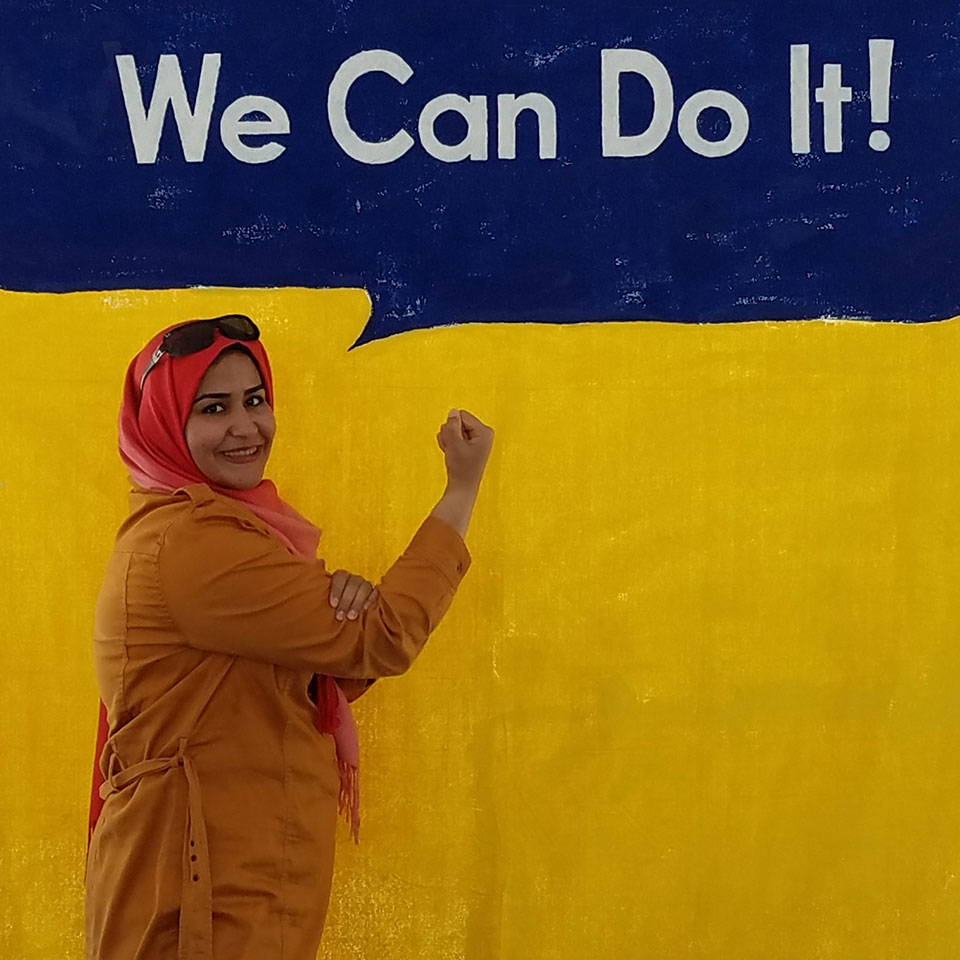 "Woman flexing her right arm against a yellow background with a speech bubble reading ""We Can Do It!"""