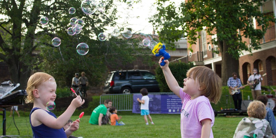 Two children play with bubbles on a lawn. Musicians play on a stage in background as crowds watch.