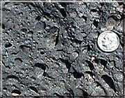 A section of basalt with a dime for size reference
