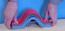 Folded foam boards with string, displaying mountain folds, by being pushed toward the middle