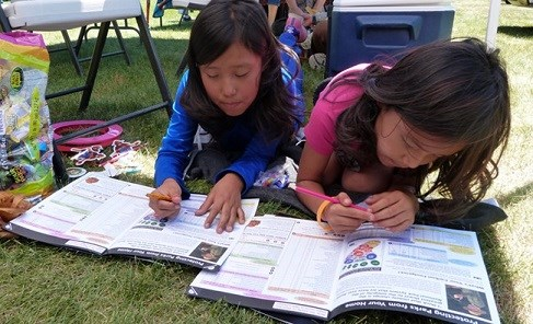 Two park visitors working on completing their Junior Ranger Books.