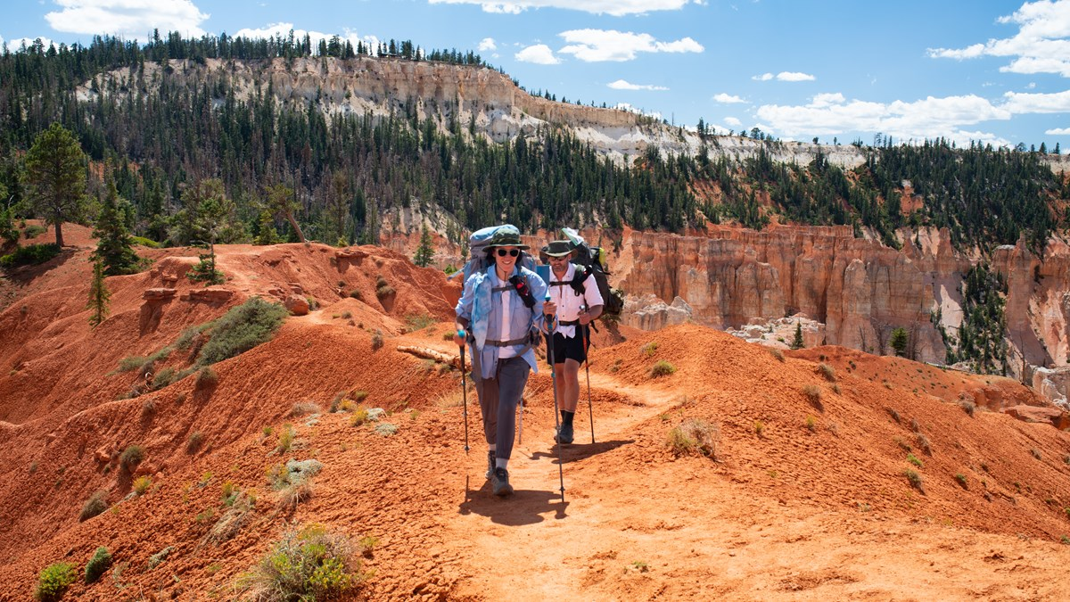 Two backcountry hikers along red rock path