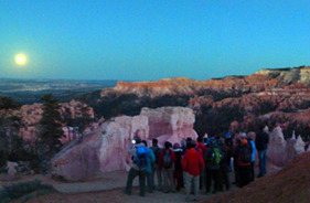 Ranger leads hike into canyon under moon rise.