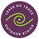 "purple circle with a green wave graphic in the middle and the words ""Leave No Trace Outdoor Ethics"" in white around the inside edge of the circle"