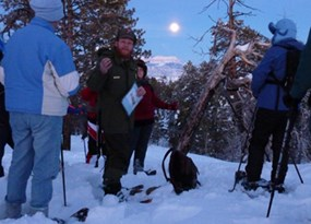 Ranger standing with group on snowshoe with moon rising over distant plateau