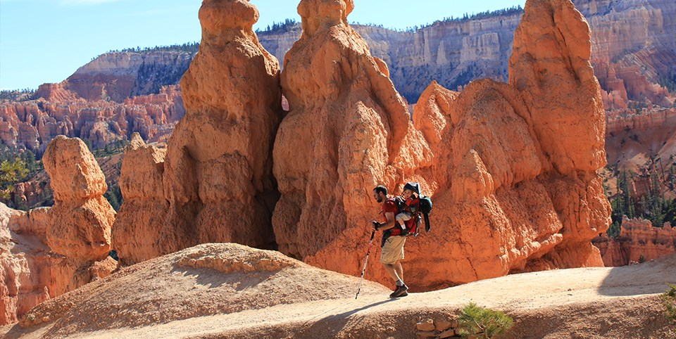 Man carries child on back along trail surrounded by red rock spires
