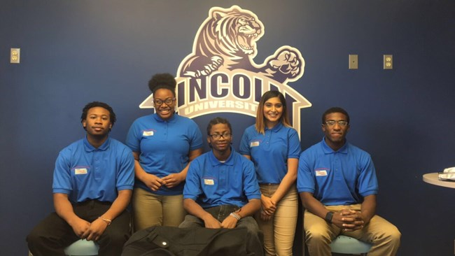 Five members of the youth leadership academy in a group photo in front of Lincoln University logo.
