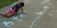 "A young girl writes ""bring people together"" in chalk on the sidewalk."