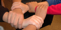 Image of five hands grabbing the wrist of the person next to them, interlocked.