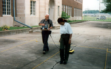 Image of man and woman pulling ground penetrating radar unit across concrete sidewalk.