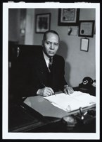 Charles Hamilton Houston, seated at desk. Photo, 1939.