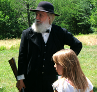 Young student with living history actor protraying John Brown at Black Jack Battlefield and Nature Park in Kansas.