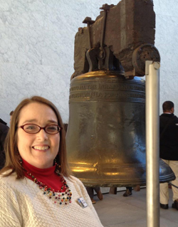 Ranger Cheryl smiles in front of the Liberty Bell at Independence National Historical Park.