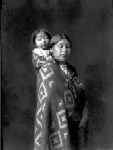 Indian woman in blanket, with small child on back by J.A. Shuck.